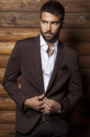 Portrait der jungen schönen modischen Mann gegen Holzwand