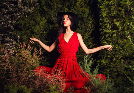 Beauty brunette women in red dress   hat pose at night park  photo