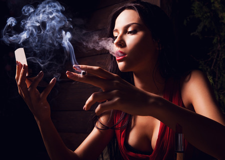 Attractive young women looking on mirror and smoke cigarette  photo