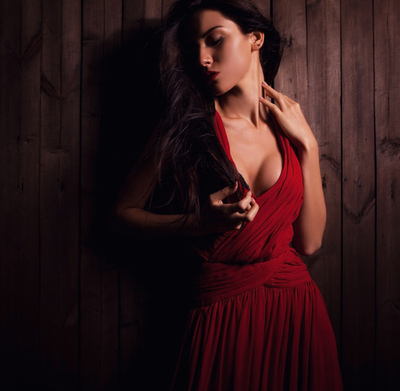 Lady in red pose on wooden .Close-up photo  photo