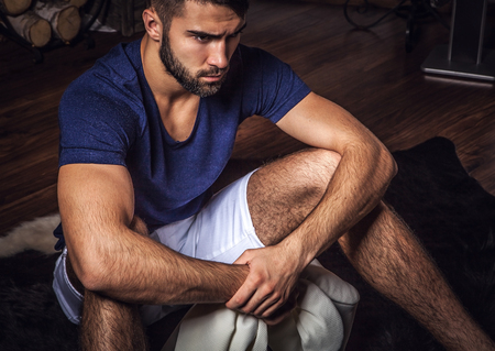 25s: Young attractive bearded men pose in modern room  Close-up photo  Stock Photo