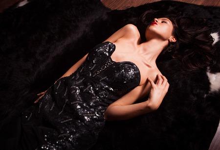 womanly: Beauty fashion Women Portrait  Model pose in luxury dress on black fur  Stock Photo