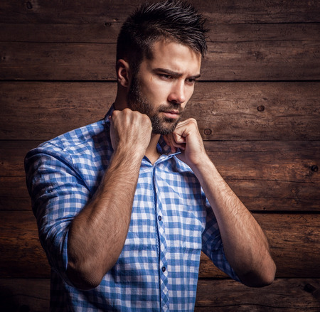 Portrait of young beautiful fashionable man against wooden wall  photo