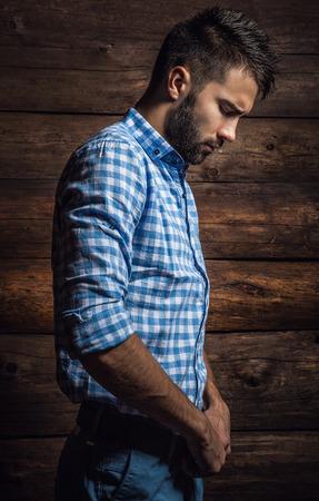 poses de modelos: Retrato del hombre hermoso joven de moda contra la pared de madera