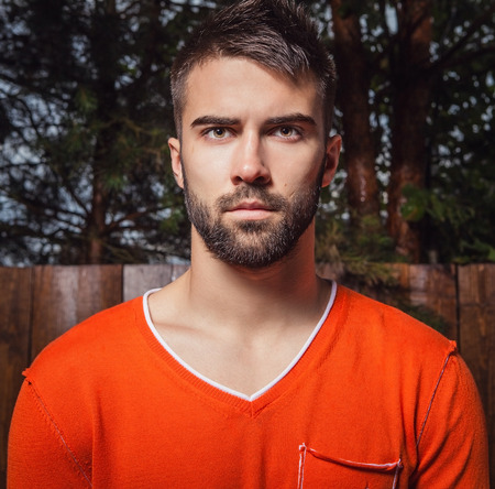 Portrait of young beautiful man in orange, against outdoor  photo