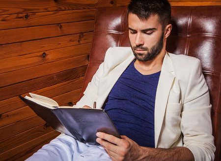 Handsome young man in white suit relaxing on luxury sofa with diary  photo