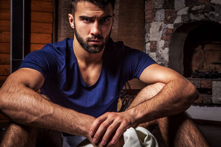 Young attractive bearded men pose in modern room  Close-up photo  photo