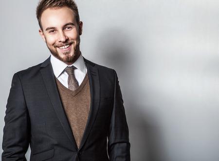 Elegant & Positive young handsome man in costume. Studio fashion portrait.