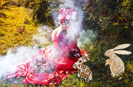 Fashion image of sensual girl in bright red fantasy stylization. Outdoor fairy tale art photo. photo