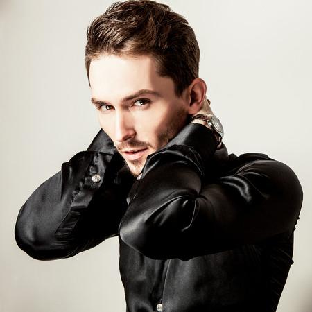 Elegante junge stattlicher Mann im schwarzen Seidenhemd. Studio Mode Porträt.