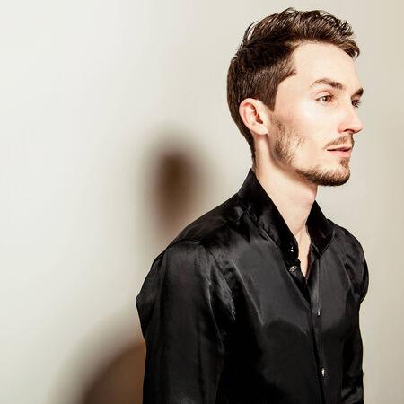 black silk: Elegant young handsome man in black silk shirt. Studio fashion portrait.