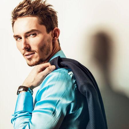 Elegant young handsome man in blue silk shirt. Studio fashion portrait. photo