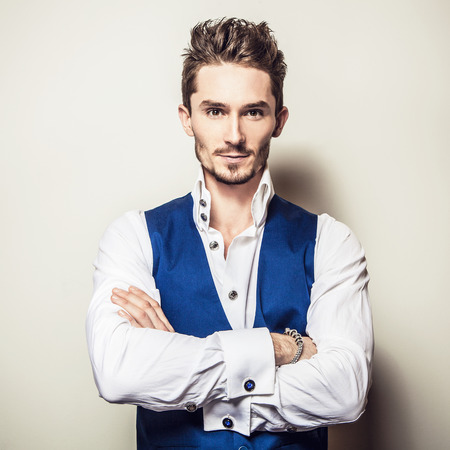 young male: Elegant young handsome man in white shirt & vest. Studio fashion portrait.