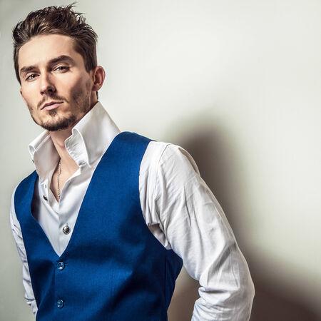 Elegant young handsome man in white shirt & vest. Studio fashion portrait. photo