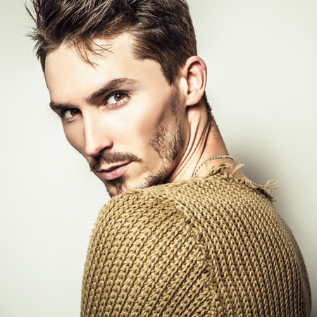 Studio portrait of young handsome man in knitted sweater. Close-up photo. photo