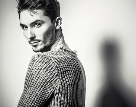 blackwhite: Black-white studio portrait of young handsome man in knitted sweater. Close-up photo. Stock Photo