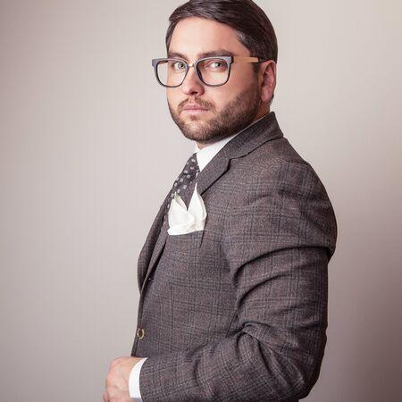 Elegant young handsome man in grey costume. Studio fashion portrait.