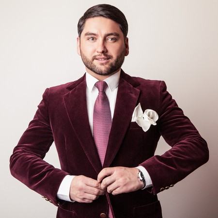 Elegant young handsome man in luxury velvet claret costume. Studio fashion portrait. photo