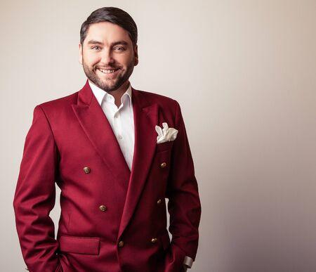 Elegant young handsome man in luxury red costume. Studio fashion portrait. photo