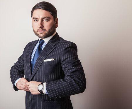 Elegant young handsome man in luxury dark blue costume. Studio fashion portrait. Stock Photo