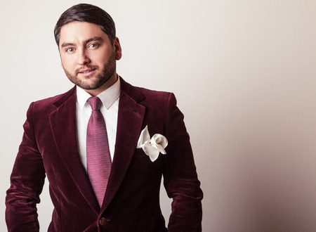 Elegant young handsome man in luxury velvet claret costume. Studio fashion portrait.