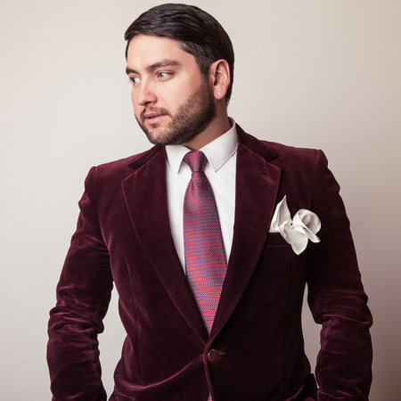 claret: Elegant young handsome man in luxury velvet claret costume. Studio fashion portrait.