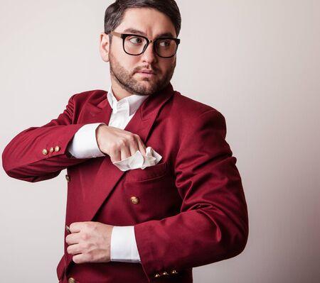 Elegant young handsome man in luxury red costume. Studio fashion portrait.