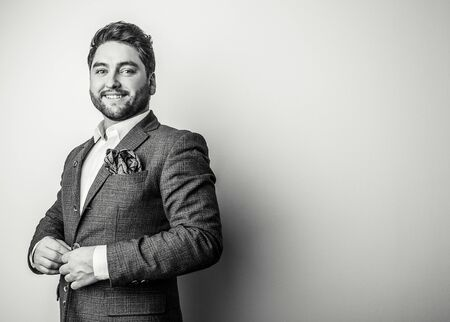 Elegant young handsome man in grey costume. Black-white studio fashion portrait. Stock Photo