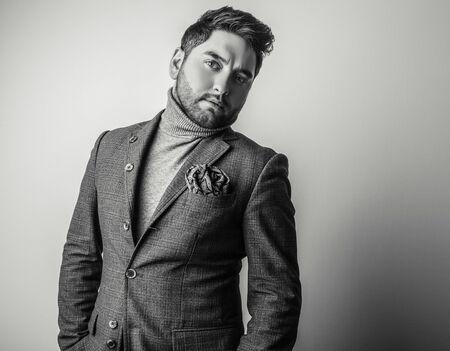 blackwhite: Elegant young handsome man in grey costume. Black-white studio fashion portrait. Stock Photo