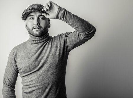 Elegant young handsome man in grey sweater. Black-white studio fashion portrait. Stock Photo