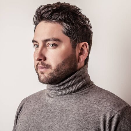 Elegant young handsome man in grey sweater. Studio fashion portrait. Stock Photo