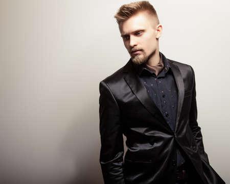 Elegant young handsome man in black costume. Studio fashion portrait. photo