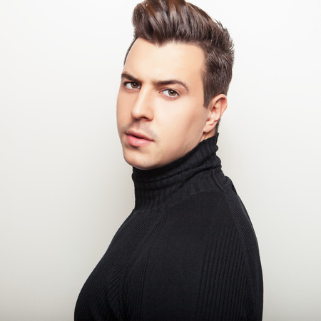 Studio portrait of young handsome man in black knitted sweater. Closeup photo. photo