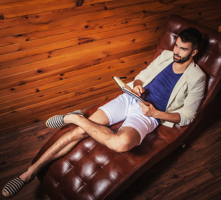 Knappe jonge man in wit pak ontspannen op luxe bank met dagboek. Stockfoto