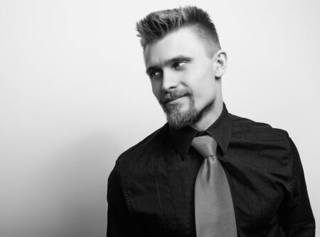 Elegant young handsome man in black shirt  tie. Blackwhite studio fashion portrait.
