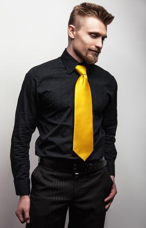 Elegant young handsome man in black shirt  yellow tie. Studio fashion portrait. photo