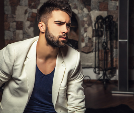 Young attractive bearded men in white suit pose in modern room. photo