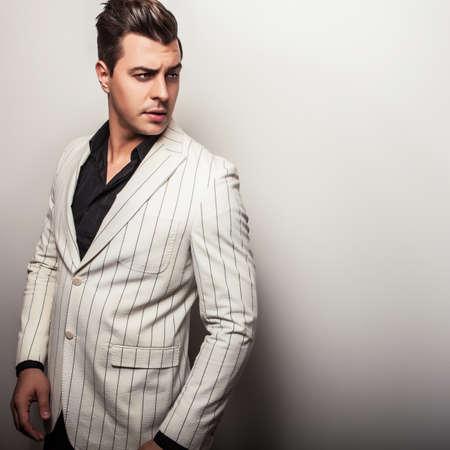 Elegant young handsome man in white costume. Studio fashion portrait. photo