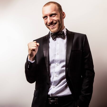 Elegant young handsome smiling man in black costume. Studio fashion portrait. photo