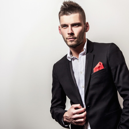 modelos hombres: Hombre apuesto joven elegante grave en traje negro. Retrato de moda Studio. Foto de archivo