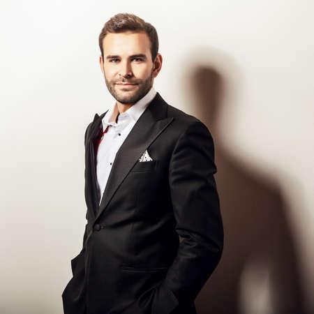 handsome: Elegant young handsome man in luxury black costume. Studio fashion portrait.