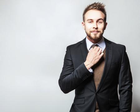 hombres guapos: Hombre joven positivo elegante y guapo en traje. Retrato de moda Studio.