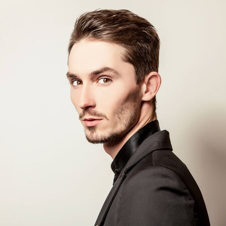 hombre con barba: Elegant young handsome man in black costume. Studio fashion portrait.