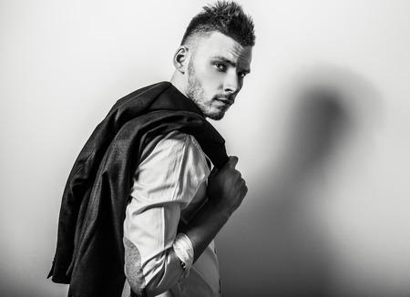 modelos hombres: Hombre apuesto joven elegante serio en la camisa blanca. Blackwhite retrato de estudio de la moda.