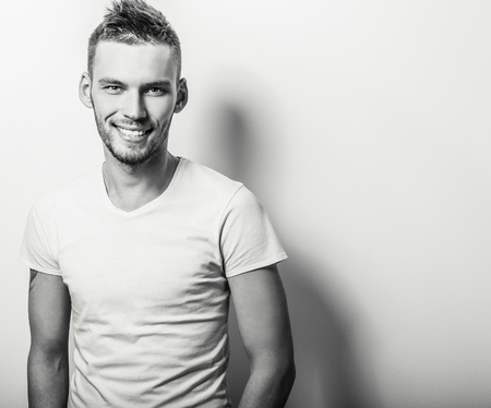 portrait: Studio portrait of young handsome man in casual white tshirt. Blackwhite closeup photo. Stock Photo