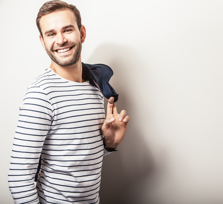 Elegant young handsome  positive man with dark blue jacket. Bright studio fashion portrait. photo