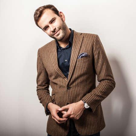 model posing: Elegant young handsome man in luxury costume. Studio fashion portrait.
