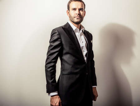 cute man: Elegant young handsome man in luxury black costume. Studio fashion portrait.