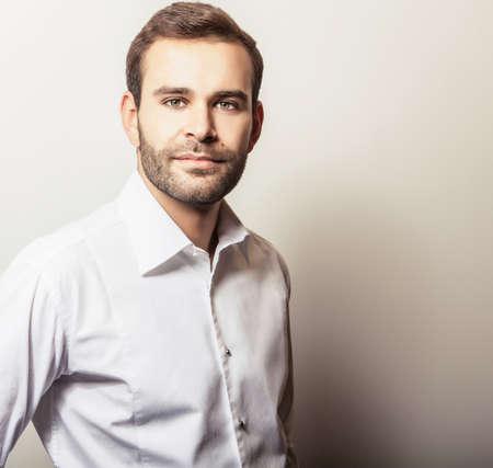 male costume: Elegant young handsome man in white shirt. Studio fashion portrait.