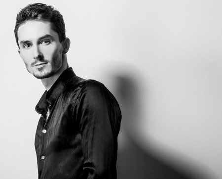 Elegant young handsome man in black silk shirt. Blackwhite studio fashion portrait.
